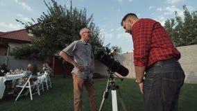 Mężczyzna ogląda teleskop na podwórku zdjęcie wideo