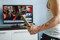 mężczyzna ogląda TV wiadomości o protestach gniewny facet roztrzaskuje TV z młotem fałszywa wiadomość powodować złość wśród widzó obrazy stock