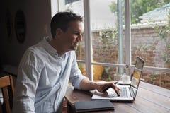 Mężczyzna ono uśmiecha się podczas gdy czytający ekran komputerowego obrazy royalty free