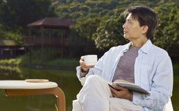 Mężczyzna ono wpatruje się daleko gdy czytać plenerowy Obrazy Royalty Free
