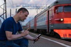 Mężczyzna opowiada na smartphone i grożeniu z jego palcem z vitiligo przy stacją kolejową zdjęcie royalty free