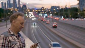 Mężczyzna opowiada na telefonie komórkowym przeciw wieczór miasta zmierzchu niebu zbiory