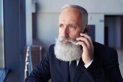 Mężczyzna opowiada na telefonie z grzebak twarzą podczas gdy przyglądający okno out Zdjęcia Royalty Free