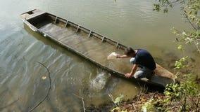 Mężczyzna opróżnia starą zapadniętą łódź rybacką zbiory