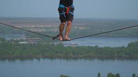 Mężczyzna ostrożnie chodzi wzdłuż arkany wzdłuż highline przeciw tłu rzeka, zwolnione tempo zbiory wideo