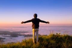 Mężczyzna otwarte ręki na górze góry z spływanie mgłą, piękny i Zdjęcia Stock