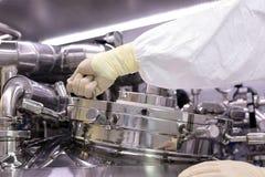 Mężczyzna otwiera chemicznego reaktor Rektor przemysł farmaceutyczny Mężczyzna zamyka reaktor Produkcja granuluje, suspen, obraz stock