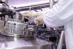 Mężczyzna otwiera chemicznego reaktor Rektor przemysł farmaceutyczny Mężczyzna zamyka reaktor Produkcja granuluje, suspen, obrazy stock