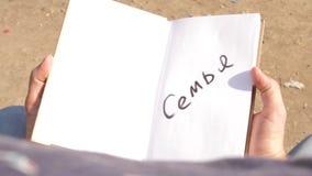 Mężczyzna otwiera książkę z wpisową «rodziną « zbiory