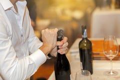 Mężczyzna otwiera wino butelkę Zdjęcie Royalty Free