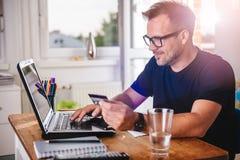 Mężczyzna płaci z kredytową kartą na laptopie Fotografia Royalty Free