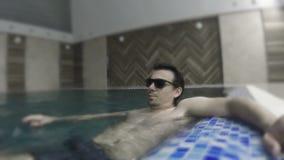 Mężczyzna pływa basenu w okularach przeciwsłonecznych zbiory