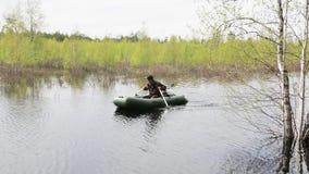 Mężczyzna pływa wzdłuż lasowej rzeki w powodzi zbiory