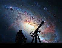 Mężczyzna patrzeje gwiazdy z teleskopem Ślimakowata galaktyka M106 obraz stock