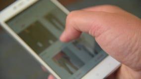 Mężczyzna patrzeje i wybiera odzież w smartphone zbiory wideo