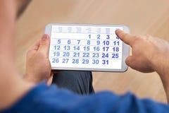 Mężczyzna patrzeje kalendarz na telefonie komórkowym Obraz Stock