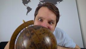 Mężczyzna patrzeje kulę ziemską i podnosi podróży miejsce przeznaczenia na leżance w domu zdjęcie wideo