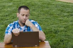 Mężczyzna patrzeje laptop outdoors Zdjęcia Royalty Free
