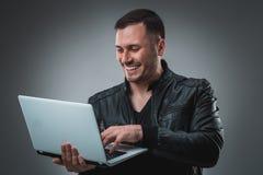 Mężczyzna patrzeje laptop w czarnej kurtce, przyrodni zwrot Trzymać rozpieczętowanego laptop i działanie emocja Obraz Royalty Free