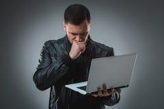Mężczyzna patrzeje laptop w czarnej kurtce, przyrodni zwrot Trzymać rozpieczętowanego laptop i działanie emocja Fotografia Stock