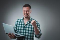 Mężczyzna patrzeje laptop w sprawdzać koszulce, przyrodni zwrot Trzymać rozpieczętowanego laptop i działanie emocja Fotografia Royalty Free