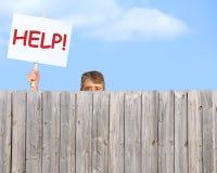 Mężczyzna patrzeje nad drewnianym prywatności ogrodzeniem z pomoc znakiem zdjęcia royalty free