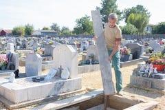 Mężczyzna patrzeje póżniej przy grób w cmentarzu zdjęcie stock