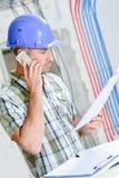 Mężczyzna patrzeje plany opowiada na telefonie komórkowym na placu budowy Fotografia Royalty Free