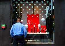 Mężczyzna patrzeje w sklepowym okno przy TAGHeuer zegarkami z rękami w kieszeniach kamera i z powrotem obrazy royalty free