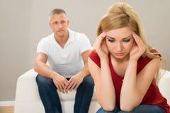 Mężczyzna patrzeje zaakcentowanej kobiety na kanapie Fotografia Stock