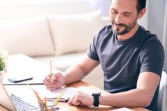Mężczyzna patrzeje zegarek podczas gdy siedzący obrazy stock