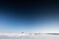 Mężczyzna pcha koło na śnieżnej powierzchni Zdjęcia Stock