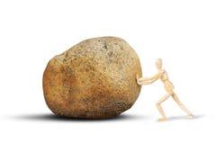 Mężczyzna pcha ogromnego kamień Fotografia Stock