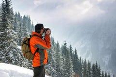 Mężczyzna photographes zima, góra krajobraz Przeciw tłu góry i sosny Obrazujący od plecy Obrazy Royalty Free