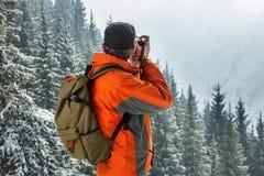 Mężczyzna photographes zima krajobraz Przeciw tłu góry i sosny obrazy stock