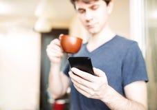 Mężczyzna pić kawowy i używać mobilnego smartphone zdjęcia royalty free