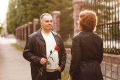 Mężczyzna pięćdziesiąt daje czerwieni róży kobieta W średnim wieku mąż i żona w lecie przy zmierzchem obraz stock