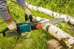 Mężczyzna piłowania drewno, używać elektryczne piły łańcuchowe Zdjęcia Stock