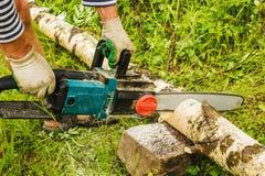 Mężczyzna piłowania drewno, używać elektryczne piły łańcuchowe Zdjęcia Royalty Free
