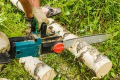 Mężczyzna piłowania drewno, używać elektryczne piły łańcuchowe Fotografia Stock