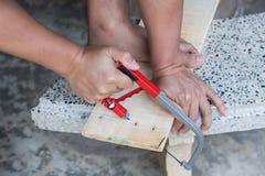 Mężczyzna piłuje deskę z ręką zobaczył drewno, w górę zdjęcia stock