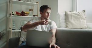 Mężczyzna pije kawę w żywym pokoju na kanapie w piżamach w ranku pracuje na jego notatniku, nowożytny projekt zdjęcie wideo