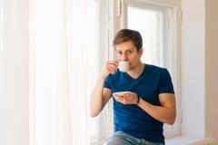Mężczyzna pije kawowy przyglądającego out okno Obraz Stock
