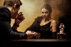 Mężczyzna pije whisky w kostiumu podczas gdy bawić się grzebaka z piękną kobietą fotografia stock