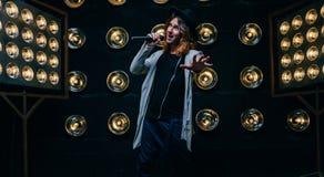 Mężczyzna piosenkarz z długie włosy, z mikrofonem na scenie obraz royalty free