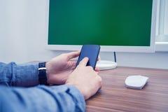 Mężczyzna pisać na maszynie na telefonie w biurze Obraz Royalty Free