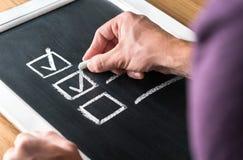 Mężczyzna pisze checkmark lista kontrolna na blackboard Dokument skończona praca i uzupełniający zadania na chalkboard fotografia royalty free