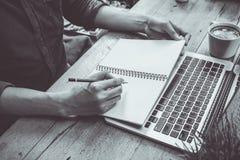 Mężczyzna pisze na notatniku z laptopem czarny i biały fotografia stock