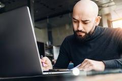 Mężczyzna pisze w notatniku i pracuje z komputerem przy stołem w sklepie z kawą Freelancer pracuje na laptopie, pisze w notatniku fotografia stock