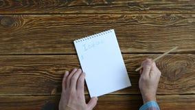 Mężczyzna pisze w notatniku Próbuje robić liście pomysły i stawia znak zapytania Na drewnianym stole zbiory